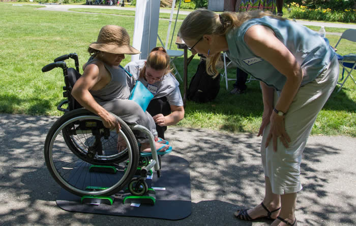 Woman in wheelchair on portable scale mat, outdoors, another woman is helping.